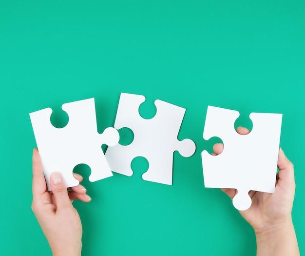 Weiße große puzzlespiele in der weiblichen hand auf grünem hintergrund