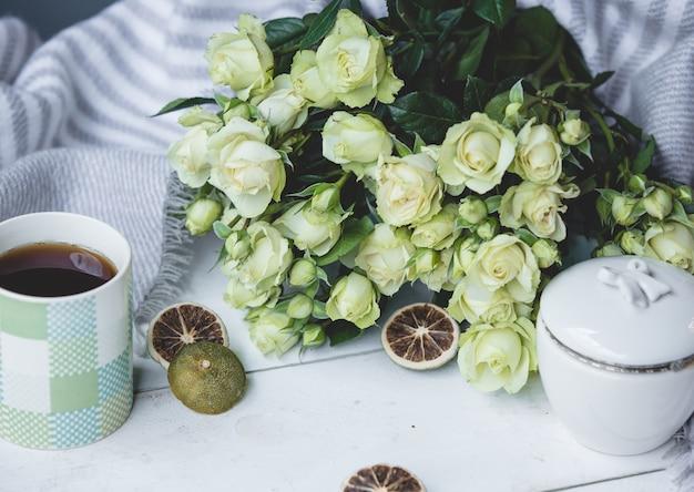 Weiße grüne rosen und eine tasse heißen tee