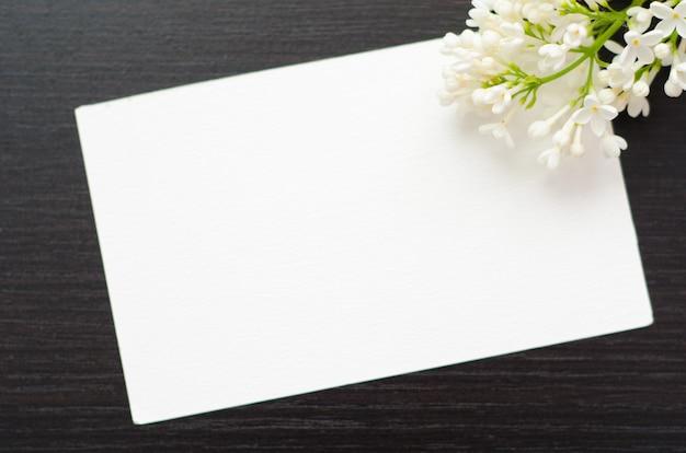 Weiße grußkarte mit blume auf einem schwarzen hintergrund