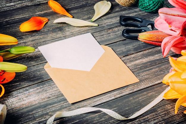 Weiße grußkarte und handwerk umschlag mit lilien blumen