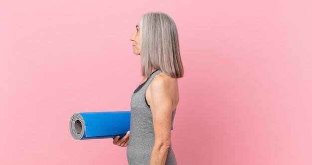 Weiße haarfrau mittleren alters auf der profilansicht, die nachdenkt, sich vorstellt oder träumt und eine yogamatte hält. fitnesskonzept