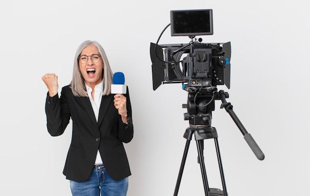 Weiße haarfrau mittleren alters, die aggressiv mit einem wütenden ausdruck schreit und ein mikrofon hält. konzept für fernsehmoderatoren