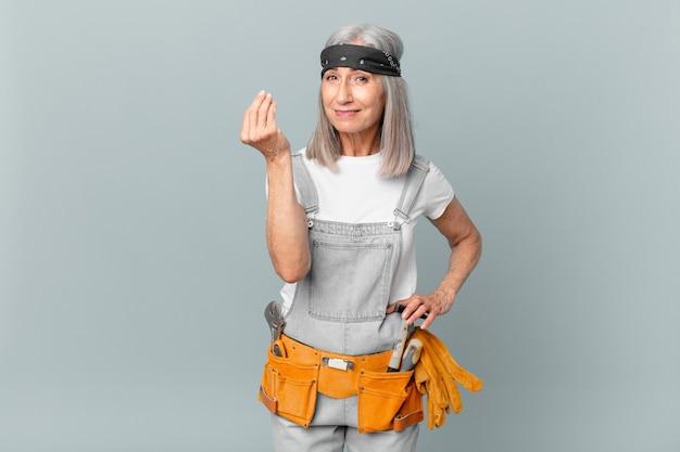 Weiße haarfrau mittleren alters, die capice oder geldgeste macht, ihnen sagt, dass sie bezahlen und arbeitskleidung und werkzeuge tragen
