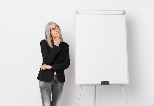 Weiße haarfrau mittleren alters, die denkt, sich zweifelhaft und verwirrt fühlt und ein brettkopierraum. geschäftskonzept