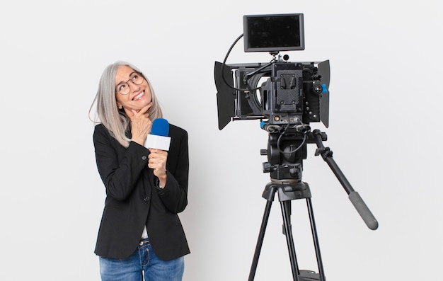 Weiße haarfrau mittleren alters, die mit einem glücklichen, selbstbewussten ausdruck mit der hand am kinn lächelt und ein mikrofon hält. konzept für fernsehmoderatoren