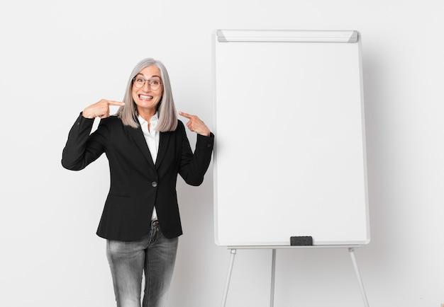 Weiße haarfrau mittleren alters, die selbstbewusst lächelt und auf ihr eigenes breites lächeln und einen brettkopierraum zeigt