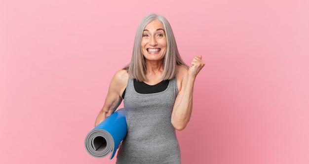 Weiße haarfrau mittleren alters, die sich schockiert fühlt, lacht und den erfolg feiert und eine yogamatte hält. fitnesskonzept