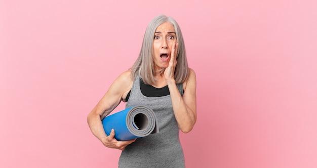 Weiße haarfrau mittleren alters, die sich schockiert und verängstigt fühlt und eine yogamatte hält. fitnesskonzept
