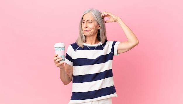 Weiße haarfrau mittleren alters, die sich verwirrt und verwirrt fühlt, den kopf kratzt und einen kaffeebehälter zum mitnehmen hält