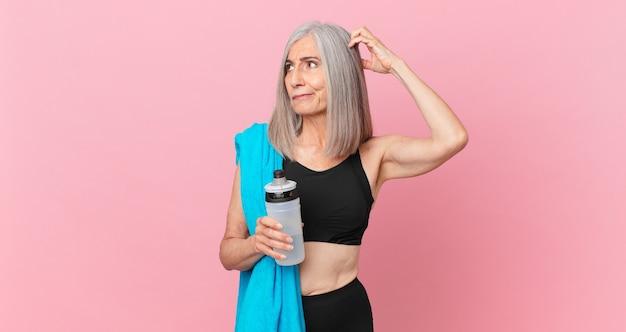Weiße haarfrau mittleren alters, die sich verwirrt und verwirrt fühlt und den kopf mit einem handtuch und einer wasserflasche kratzt. fitnesskonzept