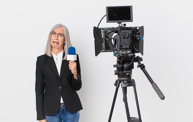 Weiße haarfrau mittleren alters, die sich verwirrt und verwirrt fühlt und ein mikrofon hält. konzept für fernsehmoderatoren