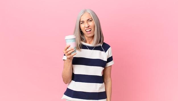Weiße haarfrau mittleren alters, die sich verwirrt und verwirrt fühlt und einen kaffeebehälter zum mitnehmen hält