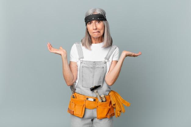Weiße haarfrau mittleren alters, die sich verwirrt und verwirrt fühlt und zweifelt und arbeitskleidung und werkzeuge trägt. housekeeping-konzept