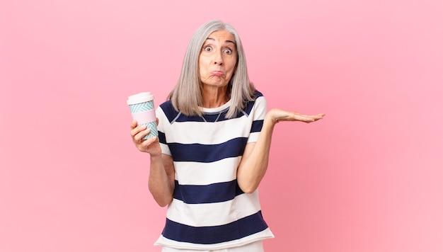 Weiße haarfrau mittleren alters, die sich verwirrt und verwirrt fühlt und zweifelt und einen kaffeebehälter zum mitnehmen hält