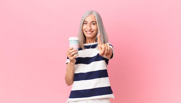 Weiße haarfrau mittleren alters, die stolz und selbstbewusst lächelt, die nummer eins macht und einen kaffeebehälter zum mitnehmen hält