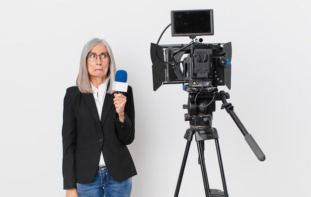 Weiße haarfrau mittleren alters, die traurig, verärgert oder wütend ist und zur seite schaut und ein mikrofon hält. konzept für fernsehmoderatoren