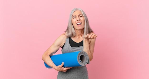 Weiße haarfrau mittleren alters, die verzweifelt, frustriert und gestresst aussieht und eine yogamatte hält. fitnesskonzept