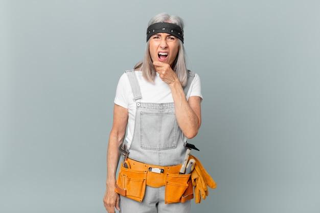Weiße haarfrau mittleren alters mit weit geöffnetem mund und augen und hand am kinn und mit arbeitskleidung und werkzeugen. housekeeping-konzept