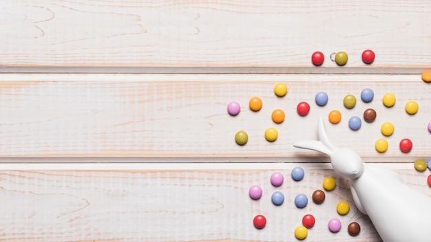 Weiße häschenfigürchen mit bunten edelsteinsüßigkeiten auf der ecke der tabelle