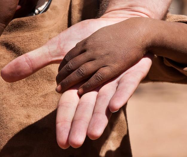 Weiße hand in der schwarzen hand