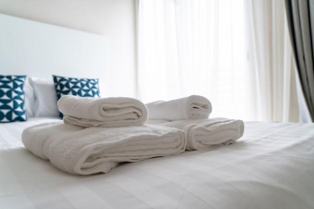 Weiße handtuchdekoration auf dem bett