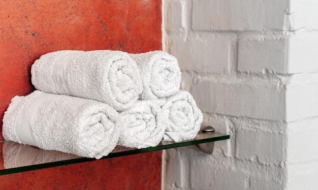 Weiße handtücher in rollen auf regal im badezimmer, im schönheitssalon oder im hotel