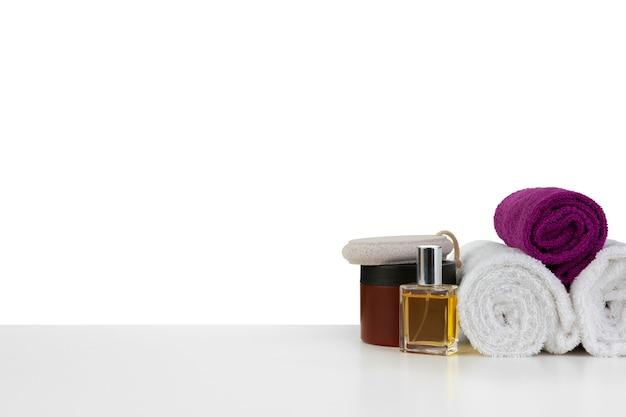 Weiße handtücher und spa-hautpflegekosmetik auf weißem hintergrund, vorderansicht