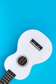 Weiße hawaiianische gitarre, ukulele auf einem schönen blauen hintergrund. platz für text
