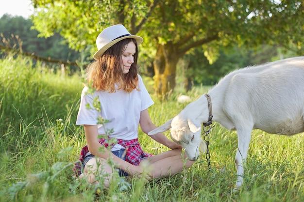 Weiße heimische bauernhofziege auf dem rasen mit teenager-mädchen