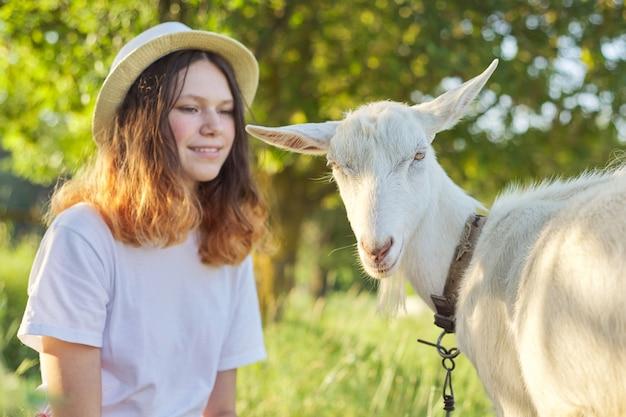 Weiße heimische bauernhofziege auf dem rasen mit teenager