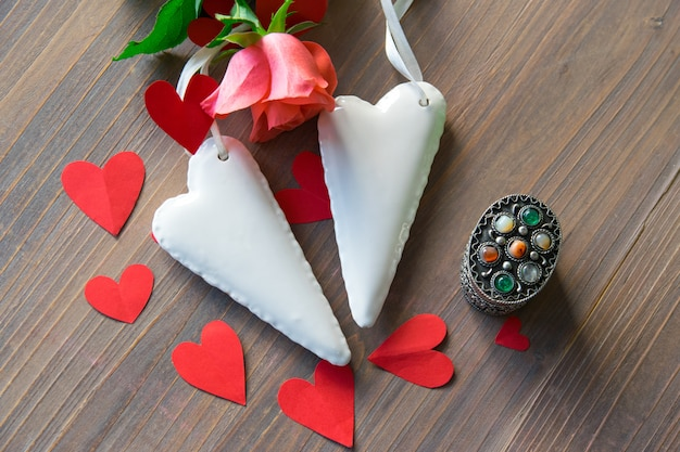 Weiße herzen des porzellans mit rosarose auf dem tisch.