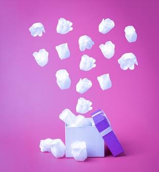 Weiße herzförmige rosenknospen fliegen aus der geschenkbox. das konzept der liebe.