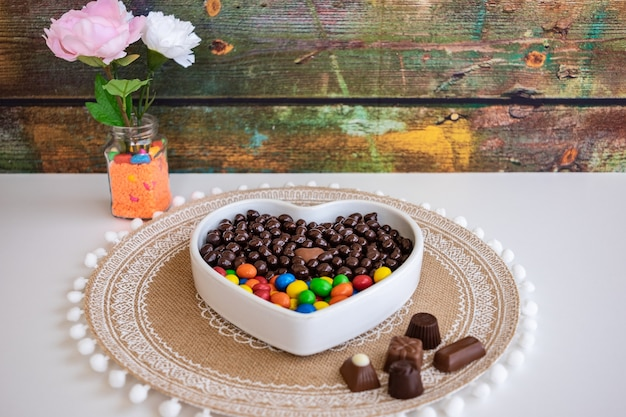 Weiße herzförmige schale gefüllt mit braunen und bunten pralinen, haselnüssen und mandeln mit schokoladenüberzug