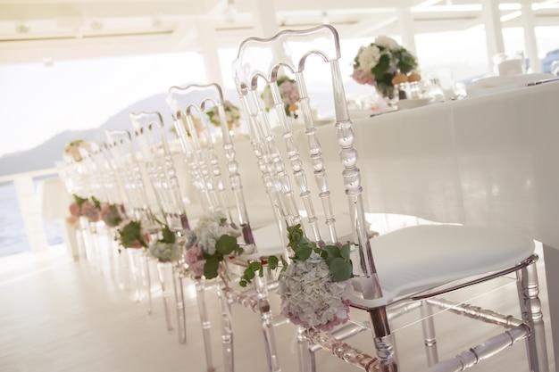 Weiße hochzeitsstühle dekoriert mit frischen blumen im restaurant mit panoramablick auf das meer. luxus-design für veranstaltung. blumenstuhldekorationen für partys und abendessen im freien. copyright-bereich für website