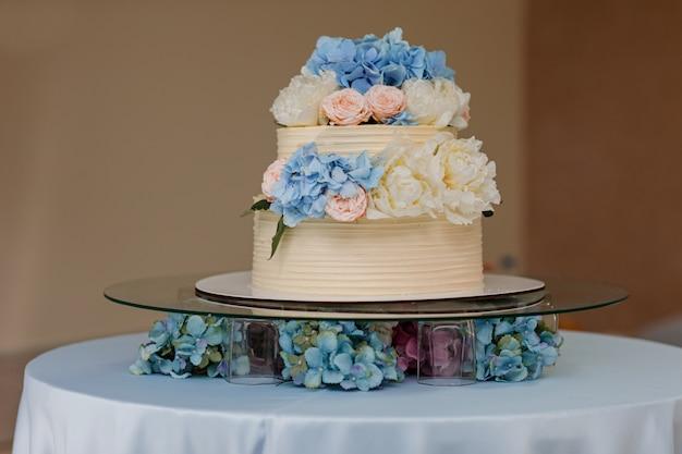 Weiße hochzeitstorte mit blauen hortensien und rosa rosenblumen auf dem tisch. stilvoller blumenhochzeitstag.