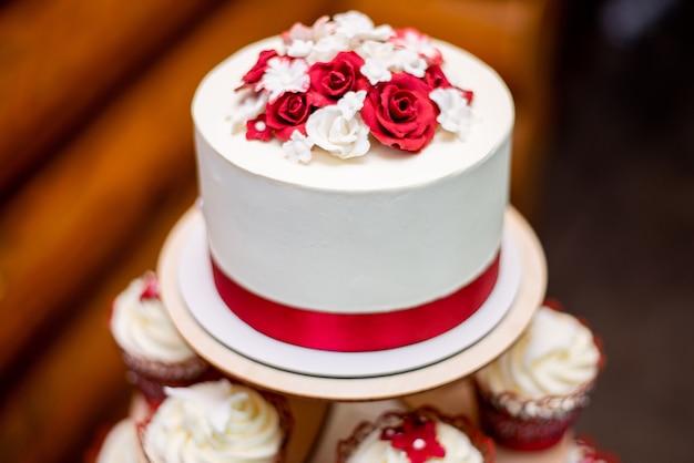 Weiße hochzeitstorte mit einem dekorativen roten band