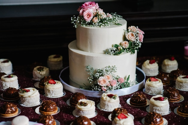 Weiße hochzeitstorte mit rosa blumen und grüns auf einem festlichen tisch mit französischem gebäck