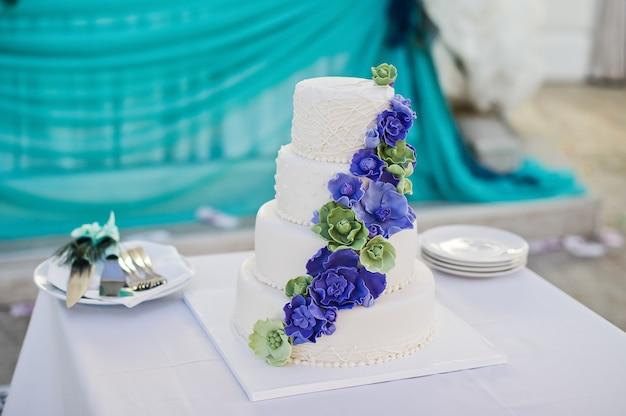Weiße hochzeitstorte verziert mit blauen blumen
