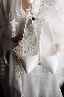 Weiße hochzeitszeremonienschuhe in den händen der braut gekleidet in seidennachtwäsche mit spitze