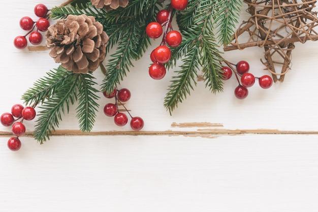 Weiße hölzerne beschaffenheit mit kiefernblatt, kiefernkegeln oder nadelbaumkegel, roten stechpalmenbällen und hölzernem stern im weihnachtskonzept. hölzerner plankenhintergrund in der draufsichtebenenlage mit kopienraum für weihnachtstapete.