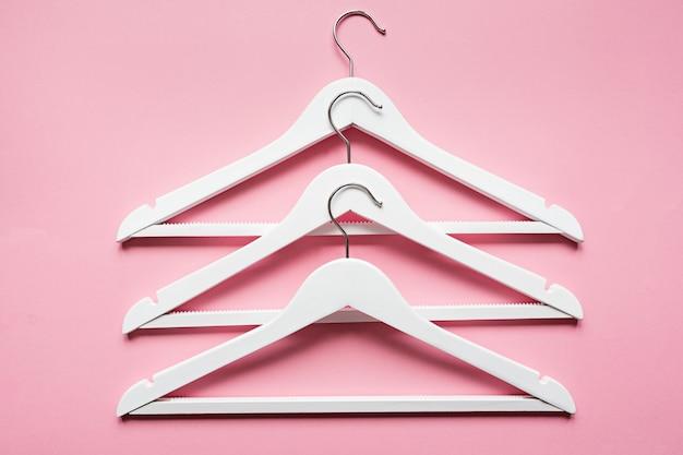 Weiße hölzerne kleiderbügel auf rosa