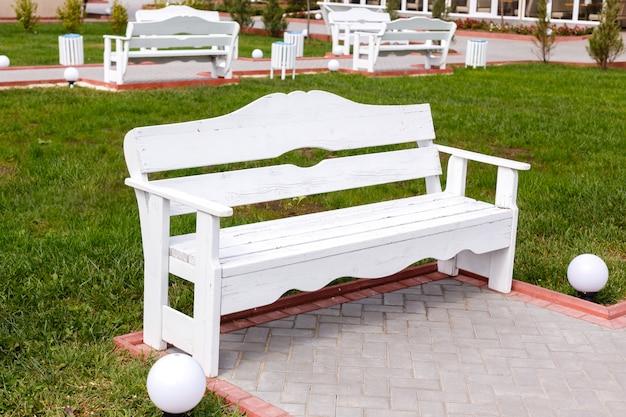 Weiße hölzerne leere bänke im stadtpark. ein guter ort, um an einem sommertag zu entspannen.