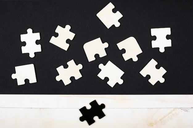 Weiße hölzerne puzzles und ein schwarzes puzzle auf einer draufsicht-draufsicht des weißen hintergrunds. weiße krähe asozial verschiedene führungsqualitäten talentierte ausgestoßene kinder lernspielzeug.