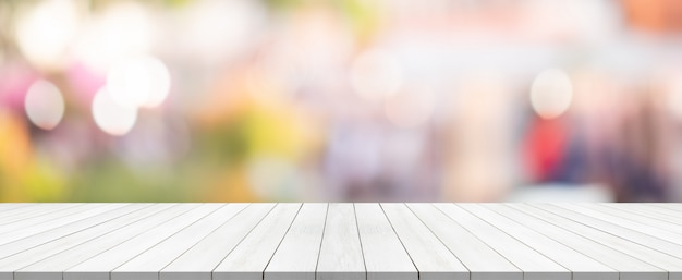 Weiße hölzerne tischplatte auf unscharfem hintergrund vom einkaufszentrum