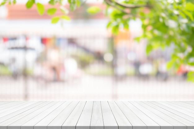 Weiße hölzerne tischplatte auf unscharfem hintergrund vom garten