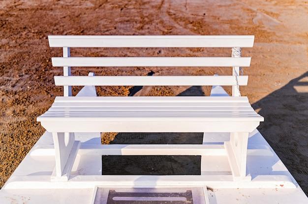 Weiße holzbank am strand. straßenfoto mit natürlicher beleuchtung. copyspace.