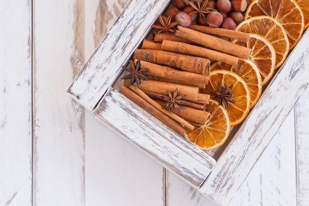 Weiße holzkiste mit aromatischen winterwürzen - getrocknete orangen, zimtstangen, anissterne und nüsse auf holzhintergrund mit kopierraum