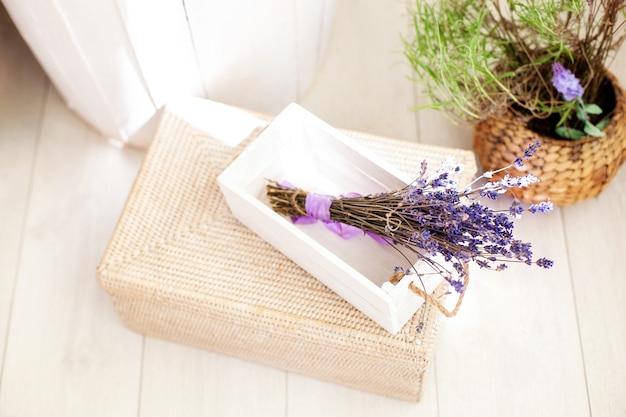 Weiße holzkiste mit lavendelblüten und violettem bogen, hochzeitsdekor. zusammengebauter lavendel zum verkauf in holzkisten und einem korb. viel lavendel im angebot. lavendelblüten. kräutermedizin, aromatherapie