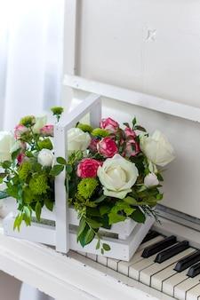 Weiße holzkiste mit weißen und rosa rosenstrauß und chrysanthemen auf weißem klavier. dekoration von zu hause. blumenkästen. hochzeitsdekoration