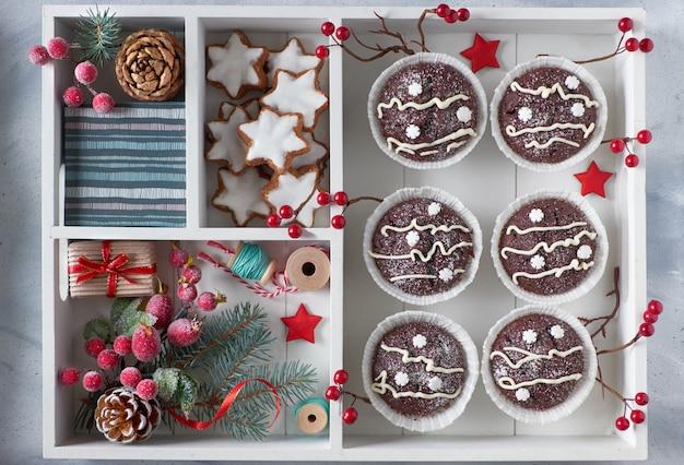 Weiße holzkiste verziert mit tannenzweigen, tannenzapfen und dekorativen beeren mit muffins und plätzchen